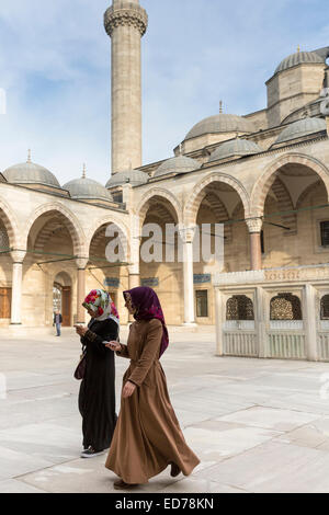 Muslim women in veil and modesty clothing in courtyard of Suleymaniye Mosque, Istanbul, Republic of Turkey - Stock Photo