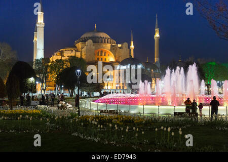 Hagia Sophia Muslim mosque museum and Atmeydani Hippodrome fountain floodlit at night, Istanbul, Turkey - Stock Photo