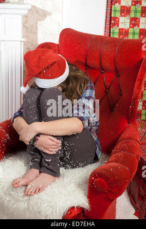 The crying girl sitting in the chair without a gift  in a Santa HAt - Stock Photo