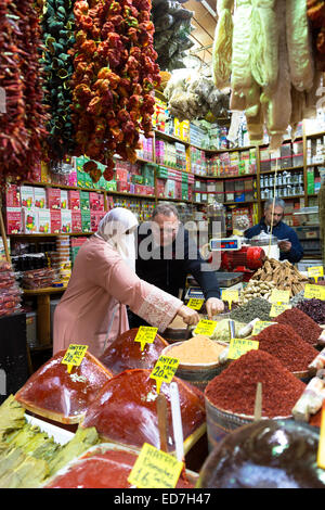 Woman shopper wearing Muslim veil buys spices in Misir Carsisi Egyptian Bazaar food and spice market, Istanbul, - Stock Photo