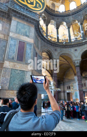 Tourist at Hagia Sophia, Ayasofya Muzesi, mosque museum using Apple Ipad tablet to take photograph in Istanbul, - Stock Photo