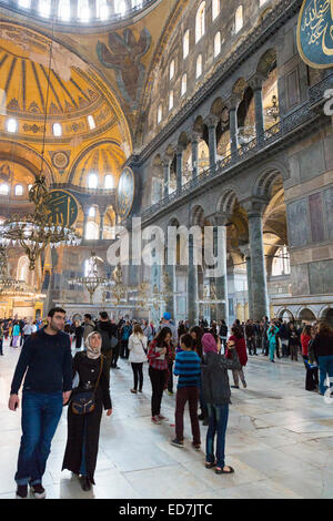 Muslim couple join tourists with smartphones at Hagia Sophia, Ayasofya Muzesi, mosque museum in Istanbul, Republic - Stock Photo