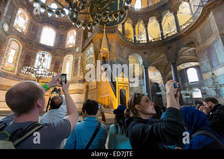Tourists at Hagia Sophia, Ayasofya Muzesi, mosque museum using smartphones to take photographs in Istanbul, Republic - Stock Photo