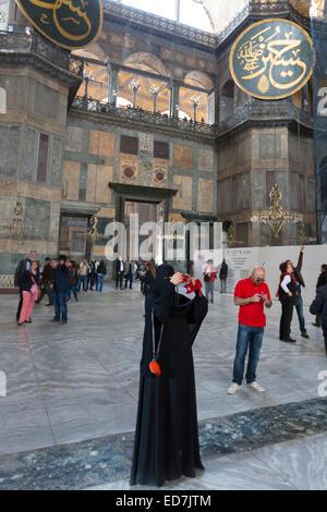 Muslim woman at Hagia Sophia, Ayasofya Muzesi mosque museum wearing niqab using smartphone taking photographs, Istanbul, - Stock Photo