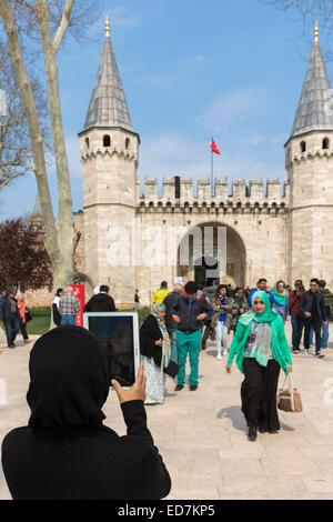 Muslim woman taking photograph with iPad tablet and tourists at Topkapi Palace, Topkapi Sarayi, in Istanbul, Republic - Stock Photo