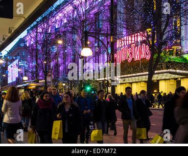 Shoppers in Oxford Street, outside Selfridge's Christmas Eve. - Stock Photo