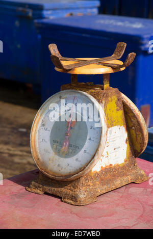 Rusting metal scales in use in a fish market Thailand - Stock Photo