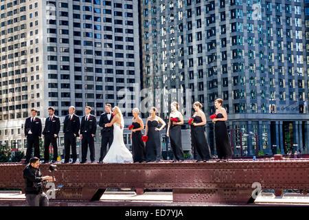 Chicago Illinois North Wabash Avenue Bridge wedding party groom bride groomsmen bridesmaids posing downtown skyscrapers - Stock Photo