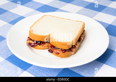 A delicious peanut butter and jelly sandwich with grape jam ready to be eaten during lunchtime. - Stock Photo