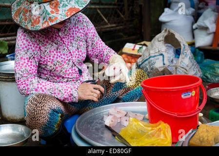 Woman preparing fish at street market in Saigon - Stock Photo