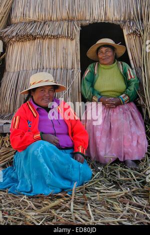 Two cute Uros Indian women on their tortora reed island, Puno, Lake Titicaca, Peru - Stock Photo