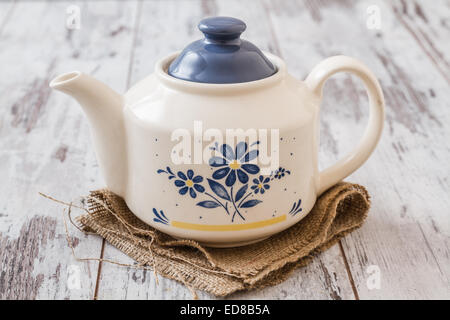 Tea in a decorative cup and teapot with linden napkin - Stock Photo