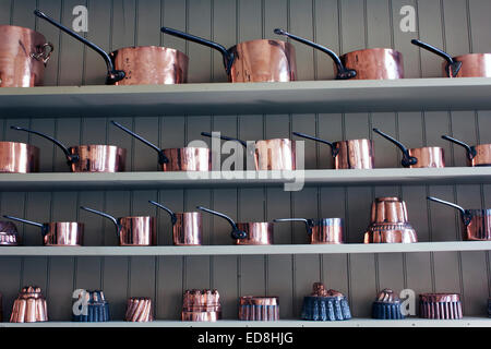 Copper Pots and Jelly Moulds lined up on kitchen shelf in England, UK. - Stock Photo