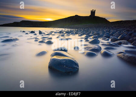 Early morning Dunstanburgh Castle silhouette - Stock Photo
