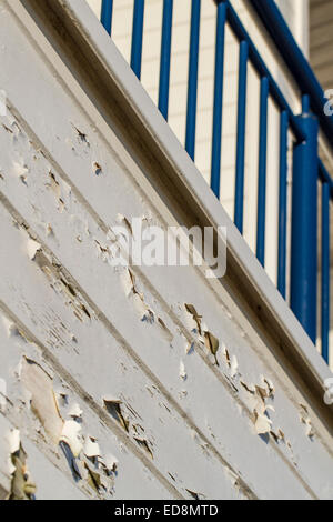 old wooden building with peeling paint and blue railing - Stock Photo