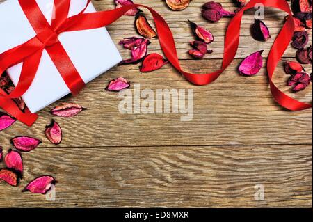 Gift box with scattered petals and ribbon on wood background - Stock Photo