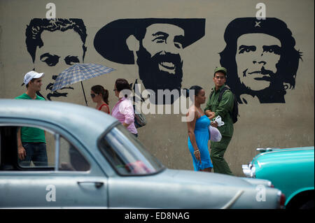 HAVANA, CUBA - JUNE, 2011: Pedestrians and classic American cars pass in front of stencil billboard of Communist - Stock Photo
