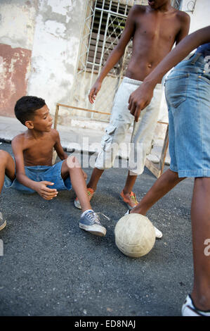 HAVANA, CUBA - JUNE, 2011: Cuban children play football together on a quiet street in Central Havana. - Stock Photo