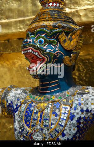 Decorative monkey demon yaksha statue at a golden phra chedi in the background at Grand Palace Bangkok Thailand - Stock Photo