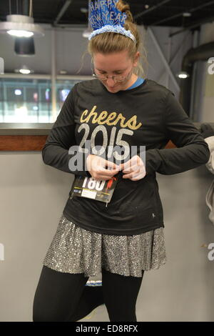 East Meadow, New York, USA. December 31, 2014. LAURA SOFTY, of Bethpage, pins on her race bib identification, in - Stock Photo