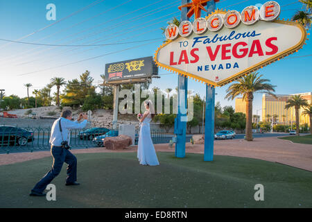 A bride is photographed at the 'Welcome to Fabulous Las Vegas sign' on the southern part of Las Vegas Boulevard. - Stock Photo