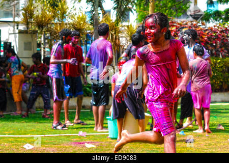 A young Indian girl covered in colored powder & water from head to toe during the celebration of spring hindu festival - Stock Photo