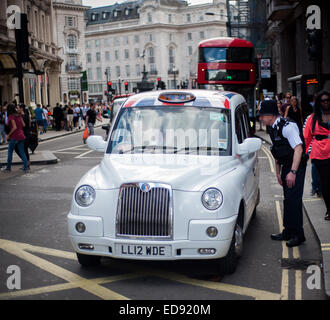 Policeman talking to London Taxi driver on Shaftesbury Avenue near Picadilly Circus, London - Stock Photo