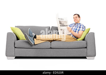 Reading Sofa | Peaceful Young Man Reading The News Seated On Sofa Isolated On White
