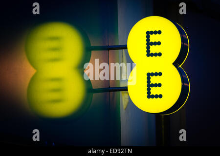 Illuminated sign logo for EE  mobile network operator and internet service provider. UK - Stock Photo