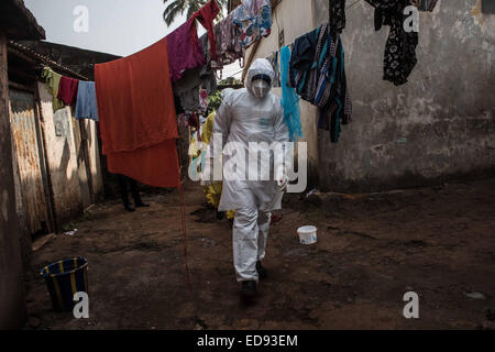 A burial team prepares to remove the body of a baby from a house in Freetown. Unsafe burials are one of the leading - Stock Photo