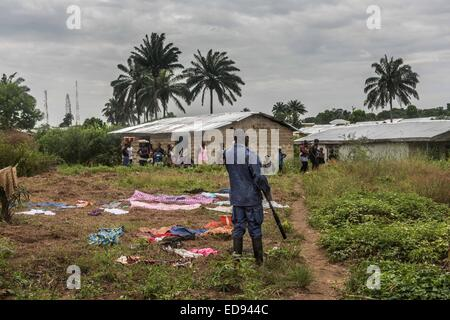 Police look on as a burial team prepares to remove the body of a woman who died in Kissi Town. The woman's family - Stock Photo