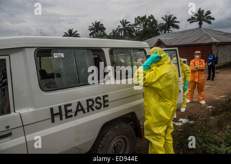 A burial team prepares to remove the body of a woman who died in Kissi Town. The woman's family had hidden her from - Stock Photo