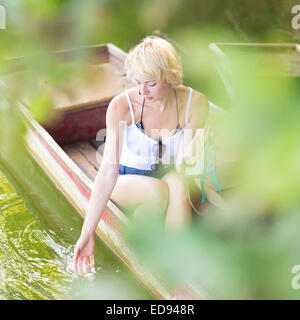 Woman relaxing on the vintage wooden boat. - Stock Photo