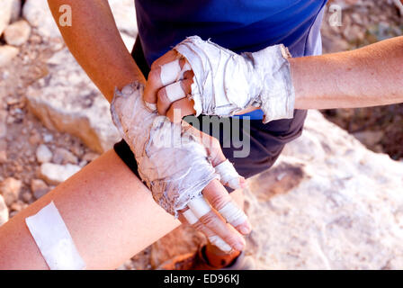 Female rock climber prepares her hands and fingers before attempting a climb in Red Rocks, Nevada - Stock Photo