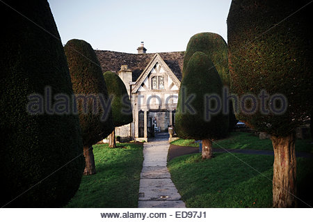 Looking down an avenue of yew trees towards the lych-gate at St.Mary's Parish Church in Painswick, Stroud, Gloucestershire, - Stock Photo