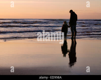 Father with toddler at the beach at sunset, Bude, Cornwall, UK - Stock Photo