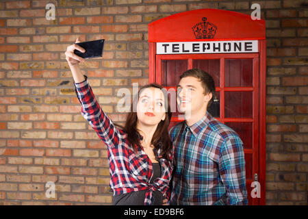 Young Couple Wearing Plaid Shirts Taking Self Portrait with Cell Phone in front of Red Telephone Booth - Stock Photo
