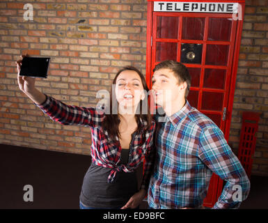 Young tourists posing in front of an iconic red British phone booth taking a selfie on their mobile phone - Stock Photo