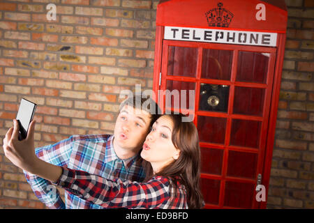 Young Sweet Couple in Chekered Shirts Taking Selfie Photos in front Telephone Booth. - Stock Photo