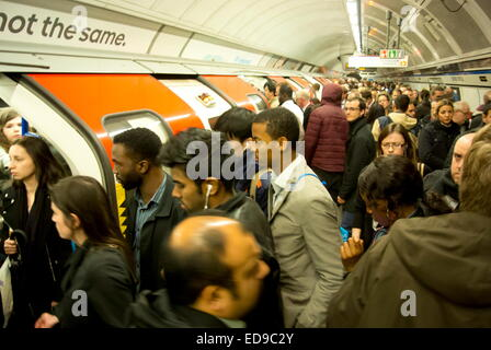Crowds of commuters board a London Underground train at Oxford Circus station on the Victoria Line, London, UK - Stock Photo
