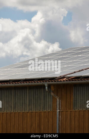 Photovoltaic solar panels on a roof for converting the solar energy of the suns radiant emissions to electricity - Stock Photo