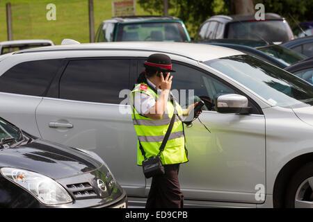 Female Traffic Warden, Civil Enforcement Officer Parking SLDC checking car - Stock Photo