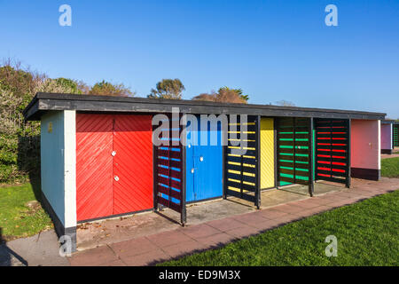 Brightly coloured row of beach huts painted in bright primary colours at Southsea, near Portsmouth, Hampshire, UK - Stock Photo
