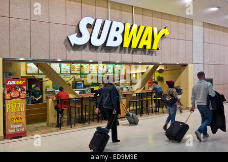 Air travelers with suitcases pass by a Subway sandwich restaurant at Toronto Airport, Canada.  Fast food meals. - Stock Photo