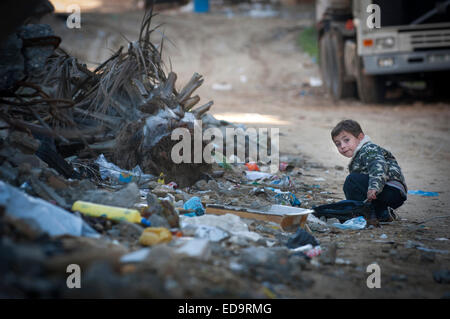 A young boy plays in the rubbish in Shujayea, Gaza Strip, Palestinian Territories. - Stock Photo