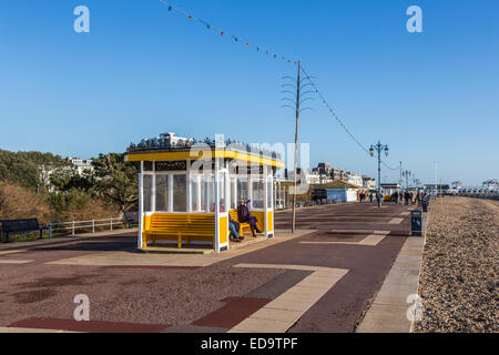 Seafront promenade at Southsea near Portsmouth with yellow shelter and a blue sky on a fine, sunny winter day - Stock Photo