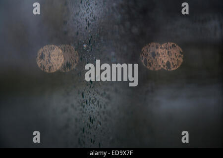 lights of traffic seen through wet windshield during rainfall in the dark - Stock Photo