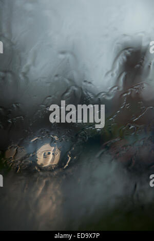 car lights and reflection seen through wet windshield during rainfall - Stock Photo