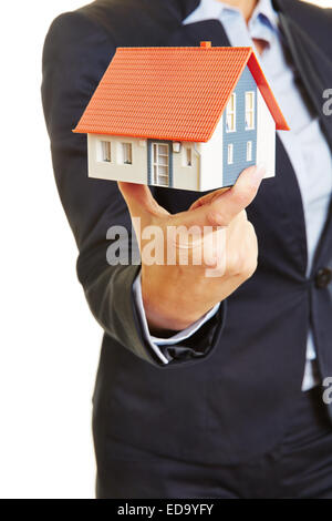 Hands of a female real estate broker holding a small house as concept for a home - Stock Photo