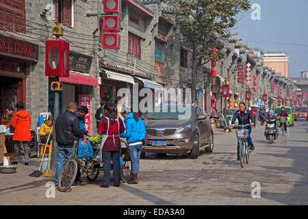 Young man with bicycle cart selling fruit on the street in the city Zhaotong, Yunnan province, China - Stock Photo